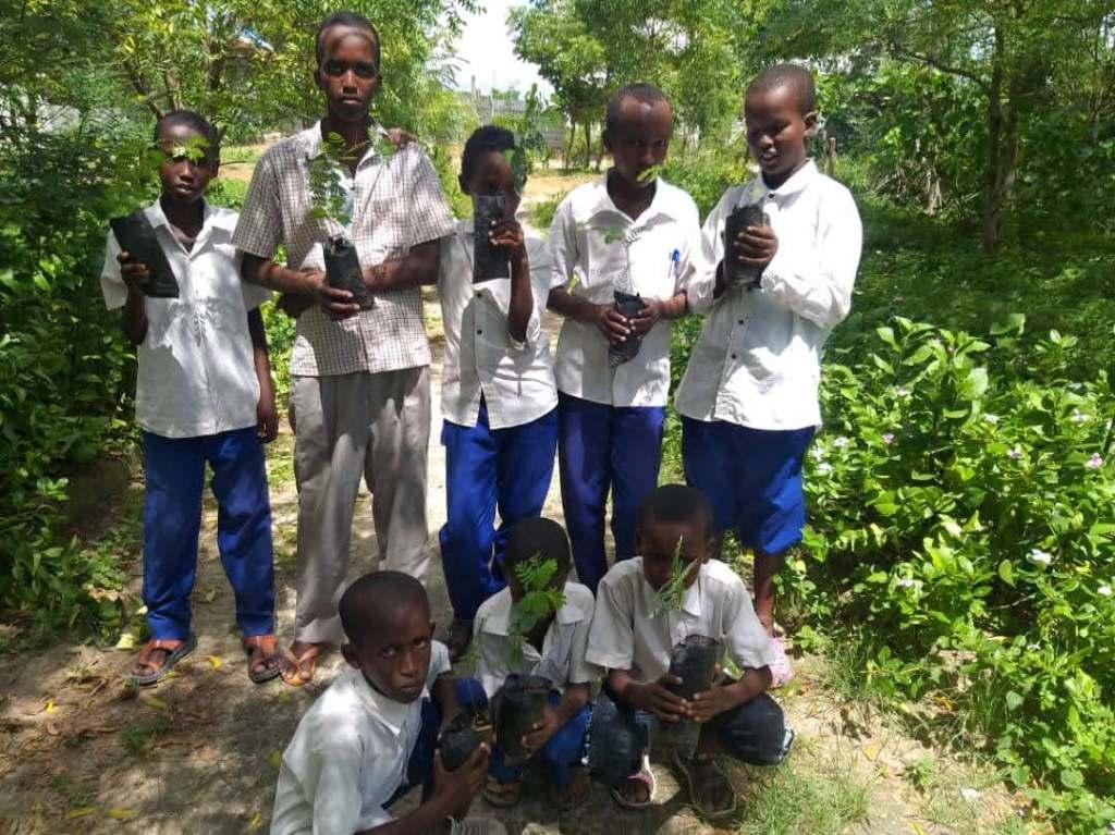 Kuvassa nuoria poikia Somaliassa istuttamassa puuntaimia
